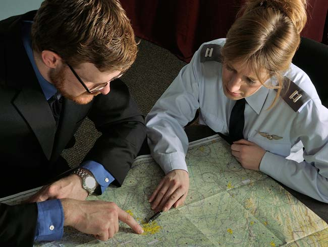 Portrait of a pilot with her client looking at a map to plan for an aerial photography flight by Allen Moore.