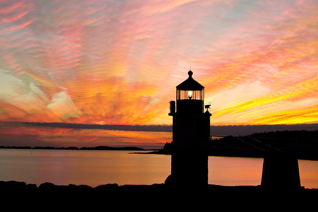 Red, orange, pink and yellow sunset image of the Marshall Point Lighthouse in Rockland, Maine created by stacking 16 images by Andy Long.