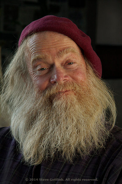 Portrait of a man with a long grey beard using ambient and flash light by Steve Gottlieb.
