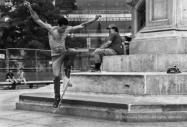 New york street photopgraphy. Black and white image of a skateboard performer at Columbus Circle in New York City. by Luca Venturi.