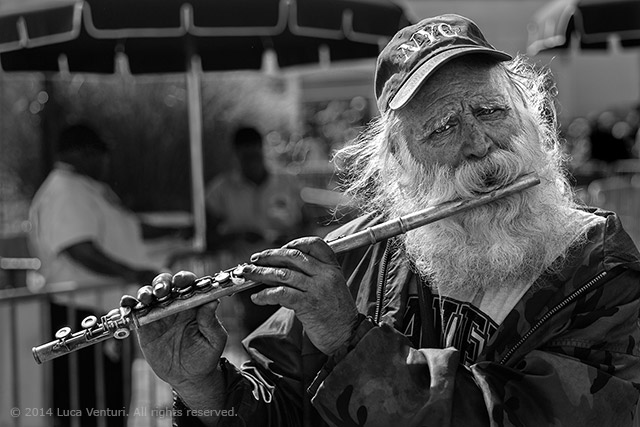 New York Street Photography. Black and white image of an old man - flute player entertaining visitors waiting to get on a ferry to Ellis Island in New York City by Luca Venturi.