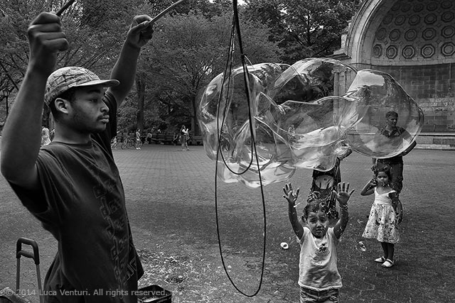 Black and white image of a man making giant bubbles and little girls trying to break them in Central Park in New York City by Luca Venturi.