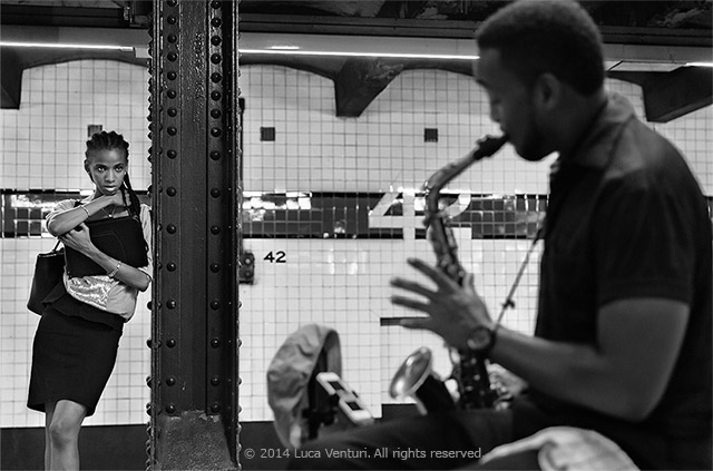 Black and white image of a saxaphone player with a girl watching at the 42nd Street subway station in New York City by Luca Venturi.