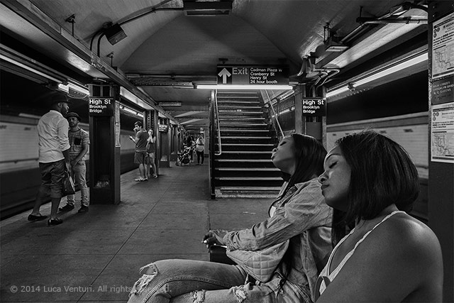 Black and white image of two girls sleeping at a subway station in New York City by Luca Venturi.