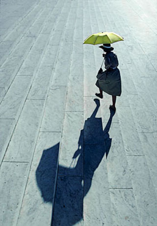 Image of a woman with a yellow umbrella going up the steps of the Jefferson Memorial in Washington D.C. by Steve Gottlieb.