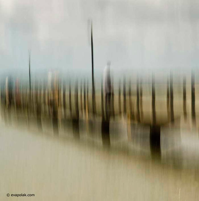Blurred image of pilings and a person near water showing progressive rhythm composition by Eva Polak.
