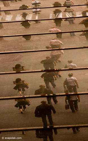 Sepia toned image of reflections ini windows of people walking showing regular rhythm composition by Eva Polak.