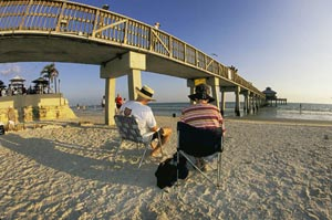 People sitting on the beach near the Estero Island bridge by Mike Goldstein.