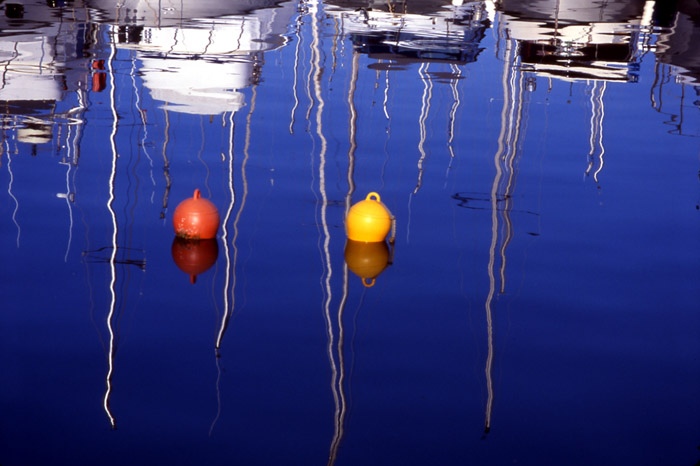 Color reflection photo of sail boats taken in French fishing port by Marie-Claire Montanari