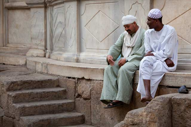 Photo of two men sitting on a stone ledge early in the morning in Cairo, Egypt by Maarten de Wolf.