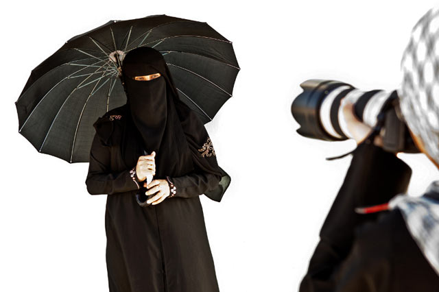 Photo of a photographer taking a photo of a Yemeni woman dressed in traditional black clothing by Maarten de Wolf.