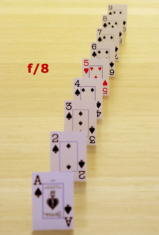 Photo of playing cards lined up in a row to show an example of depth of field with an f/8 aperture setting by Marla Meier.