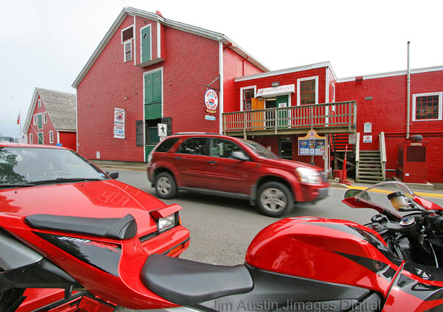 Image entitled Lunenberg Red - red building, red cars and red motocycle in Nova Scotia, Canada by Jim Autin.