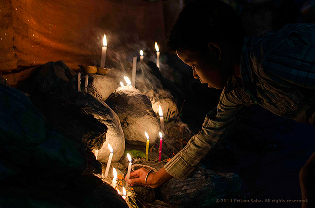 """Image of a young boy illuminated by candle light as he lights a candle on the eve of """"Chat Puja"""" near Siliguri, West Bengal, India. Image by Pritam Saha."""