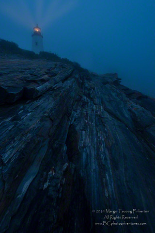The blue of twilight on the rocks leading up to a lighthouse beam of light by Margo Taussig Pinkerton.