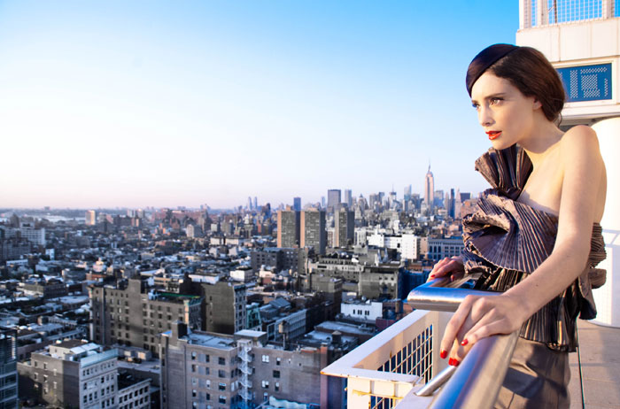 Fashion photo of woman on balcony overlooking a city by Michelle Wong