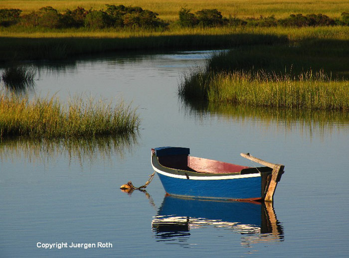 Image of a dingy and its reflection on still waters at Cape Cod by Juergen Roth.