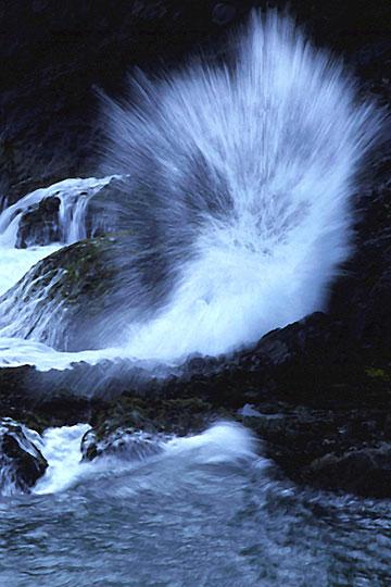 Landscape photo of wave crashing on rocks on the Oregon coast by Noella Ballenger