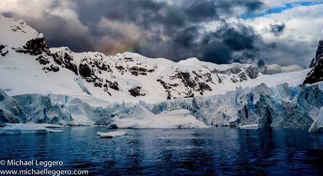 Dark stormy skies over snow covered mountains and glacier in Antarctica by Michael Leggero.