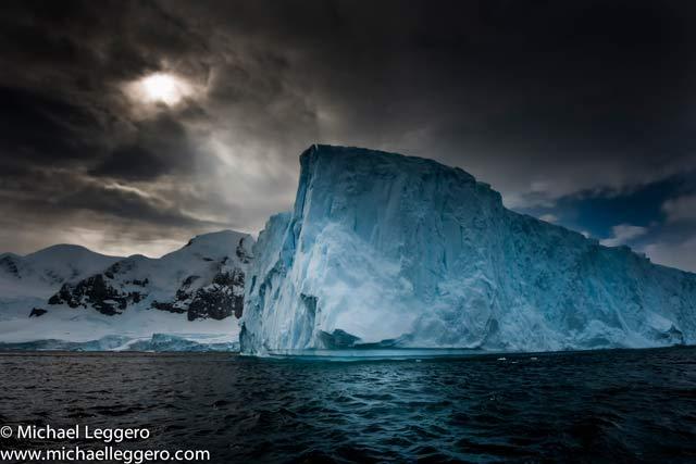 Dark stormy skies over an iceberg in Antarctica by Michael Leggero.