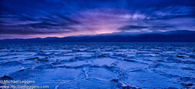 Pinkish sunlight shining through storm clouds over the dry river bed in Death Valley, easter California by Michael Leggero.