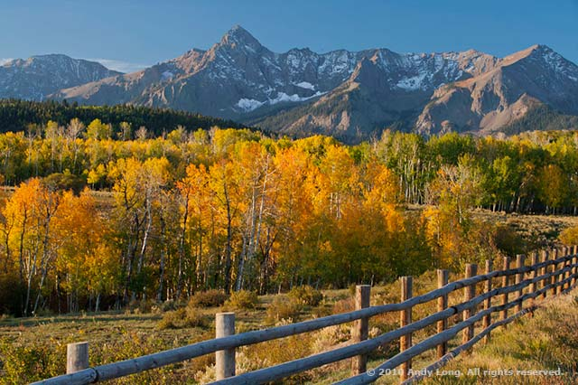 A fall scene with orange and gold trees and a fence that creates a leading line to the mountains in the background by Andy Long.