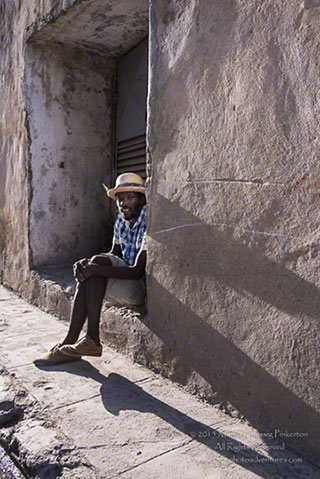 Photo of a Cuban man in a hat sitting on a step of an adobe building in Cuba by Margo Taussig Pinkerton.