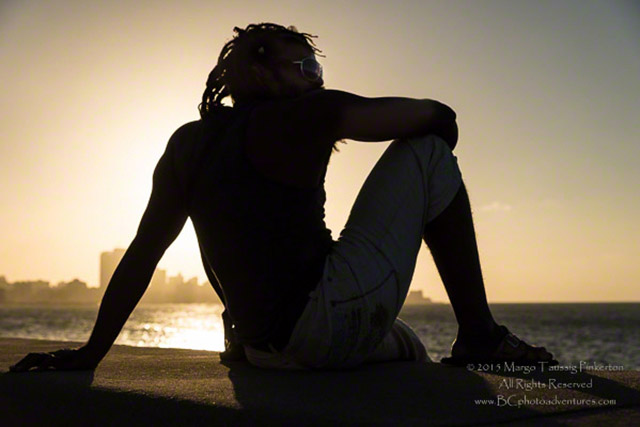 Silhouette photo of a man from Cuba sitting on a wall enjoying the sunset by Margo Taussig Pinkerton.