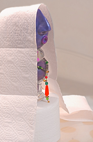 Image of sculpture sitting on toilet paper base with toilet paper cloke by Marla Meier.