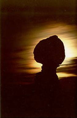 Full moon photography: silhouetted rock formations in front of full moon shrouded in clouds by Andy Long.