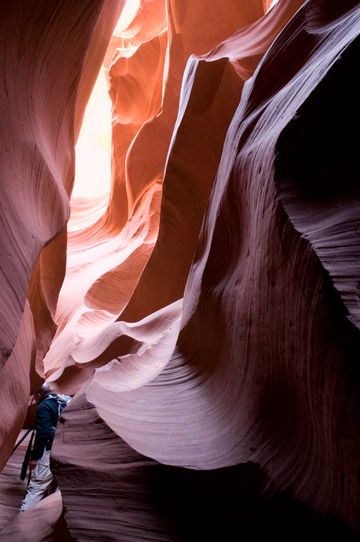Photo of rock formations and photographer with tripod in the lower canyon of Antelope Canyon by Piero Leonardi