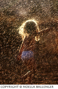 Backlighting on a little girl playing in the sprinklers by Noella Ballenger.