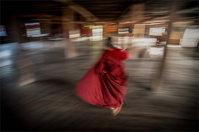motion blur photography. Motion blur showing a monk in a red robe as he escapes the photographer by Harry Fisch.