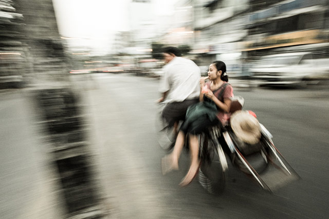 Motion is shown as a tricyclist transports a young woman in Yangoon, Mynamar by Harry Fisch.