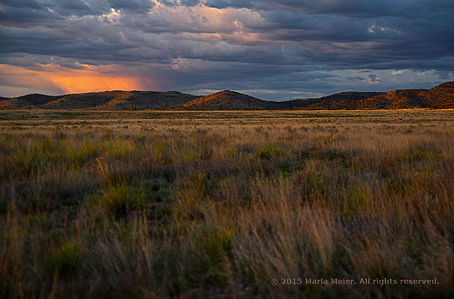 Light of an orange sunset shines through storm clouds and over the prairie and Black Hill Mountain Range in Prescott Valley, Arizona by Marla Meier.