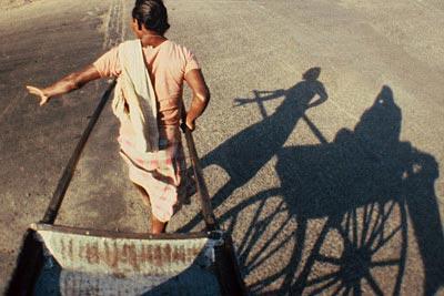 Photo of rickshaw and rickshaw shadow on street in Calcutta, India by Ron Veto