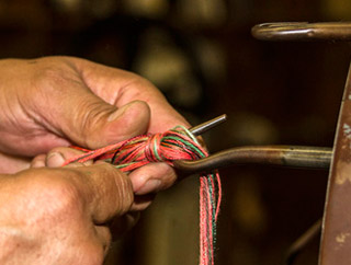 Photo of hands of man making a tassel at West Coast Trimming by Noella Ballenger