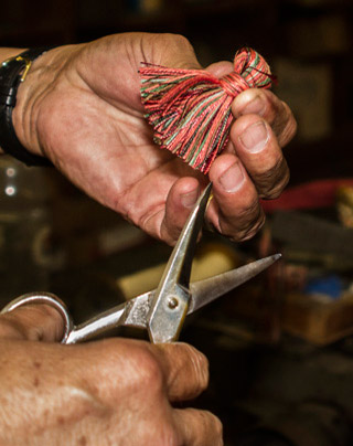 Photo of hands of man trimming a finished tassel at West Coast Trimming by Noella Ballenger