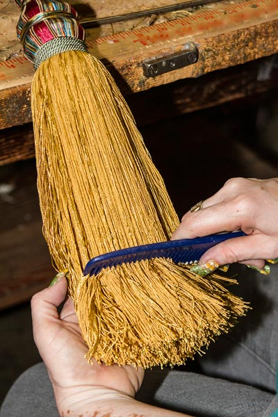 Photo of woman's hands combing a large tassel at West Coast Trimming by Noella Ballenger