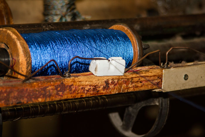 Photo of blue yarn on spooling machine at West Coast Trimming by Noella Ballenger