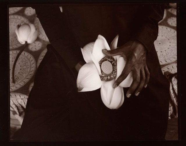 Black and white photo of a hand holding a lotus flower in Kashmir, India by Linda Connor.