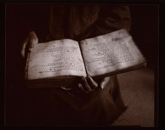 Black and white photo of Sacred Text and hands in Isreal by Linda Connor.