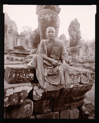 Black and white photo portrait of a young monk in Bayon, Cambodia by Linda Connor.