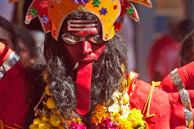 Dasara festival in India: close-up photo of person with red drooping tougue and dressed in the red and gold colors of Goddess Durga by Kris Hariharan.