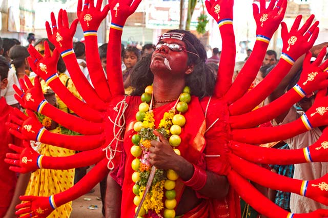Dasara festival in India: person dressed as Goddess Durga, with red and gold costume with many arms, walks the crowded streets by Kris Hariharan.