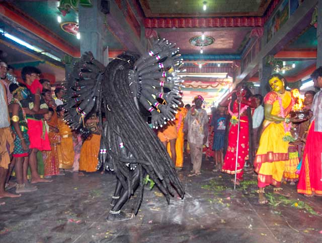 Dasara festival in India: Dancing Goddess Kali with thick long hair and numerous hands by Kris Hariharan.