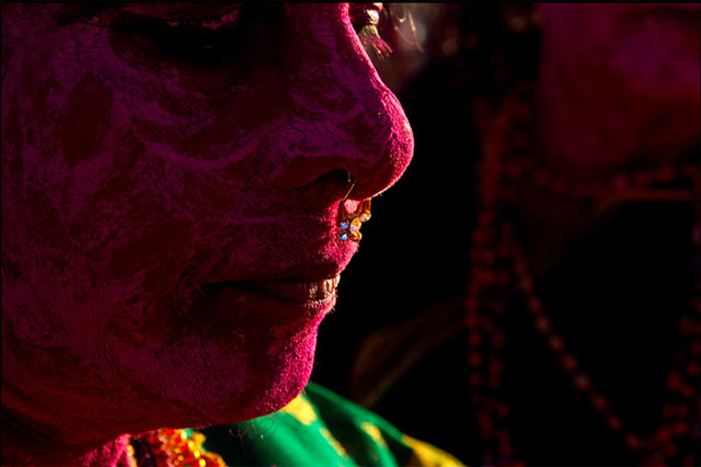 Dasara festival in India: Close-up portrait of an Indian face painted red with a colorful nose ring by Kris Hariharan.