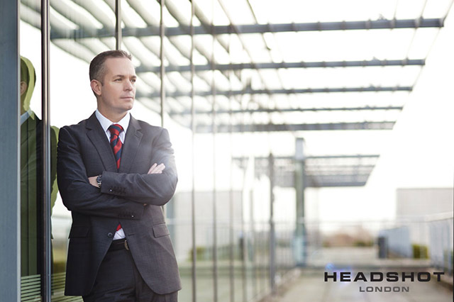 Corporate outdoor portrait of a man leaning against the glass of a building by Headshot London Photography.