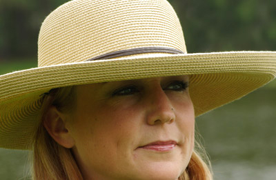 Close-up portrait of woman with hat in natural light by Marla Meier