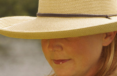 Close-up portrait of woman with hat using Lastolite gold reflector and Tiffen Warming Filter by Marla Meier